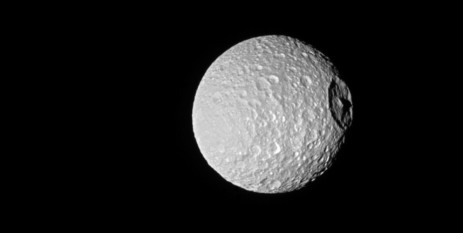 НАСА показало необычный кратер на Мимасе, обрисованый тенью - фото